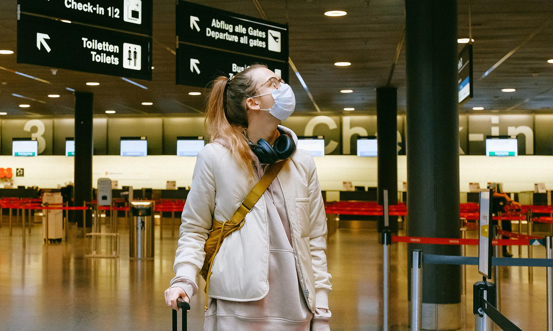 a traveler stands in an airport with a mask